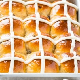 A photo of a silver cake pan of hot cross buns.