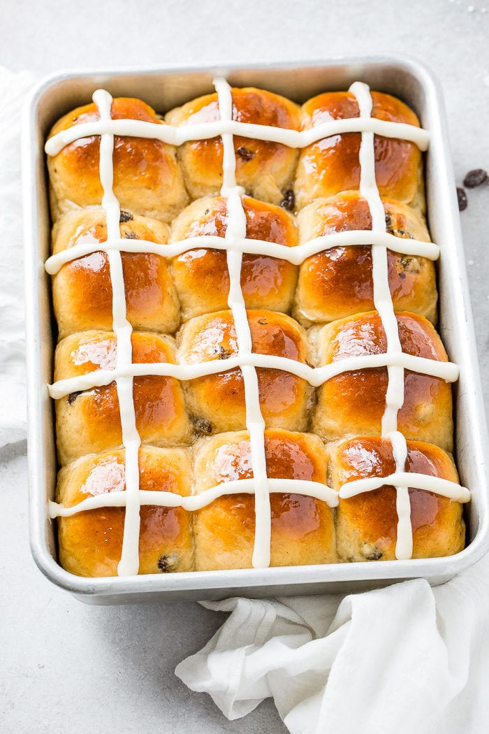 A photo looking down on a pan of hot cross buns with white frosting crosses on them.