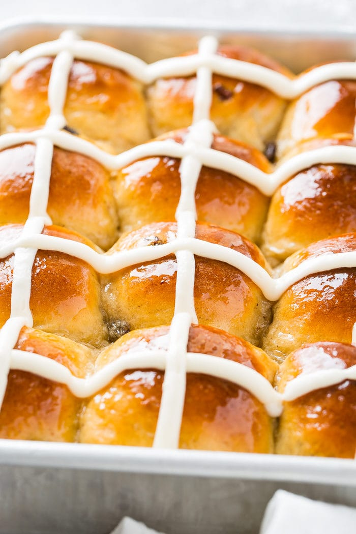 A close up photo of a pan of hot cross buns with white frosting crosses.