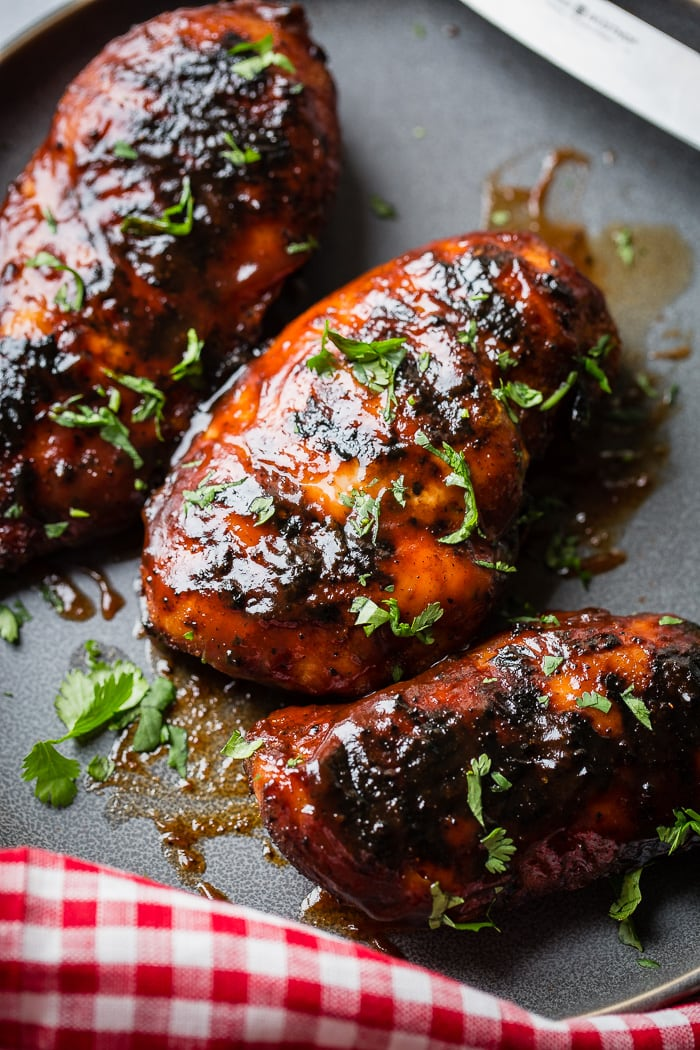 A grey plate with multiple grilled bbq sauce chicken breasts sprinkled with cilantro that has been chopped