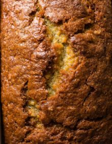 A close up of the top of the best sour cream banana bread recipe with the crack going down the center of the quick bread