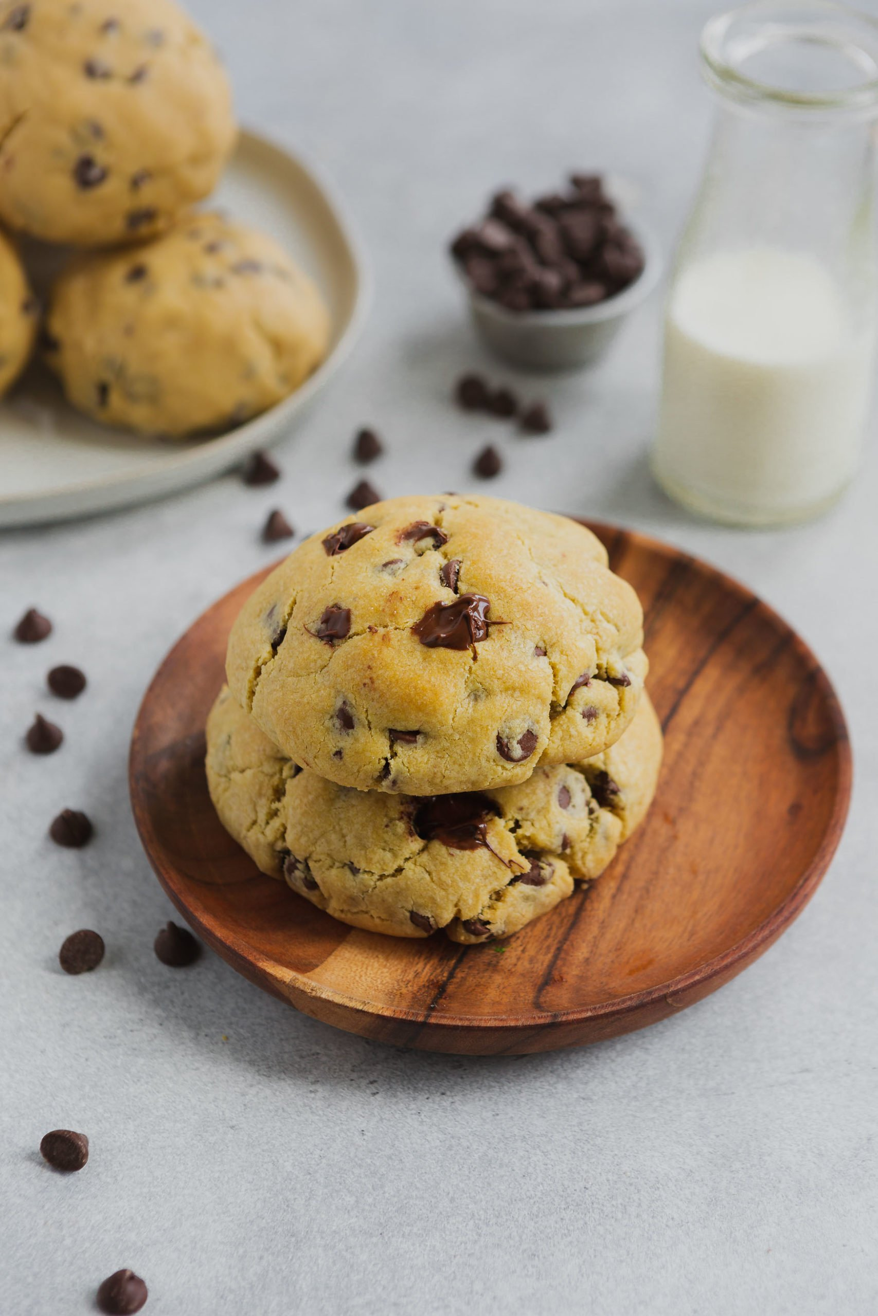 a photo of two large and thick chocolate chip cookies stacked on each other on a small wooden plate with a plate of more cookies in the background and a small cup or chocolate chips and a carafe of milk.