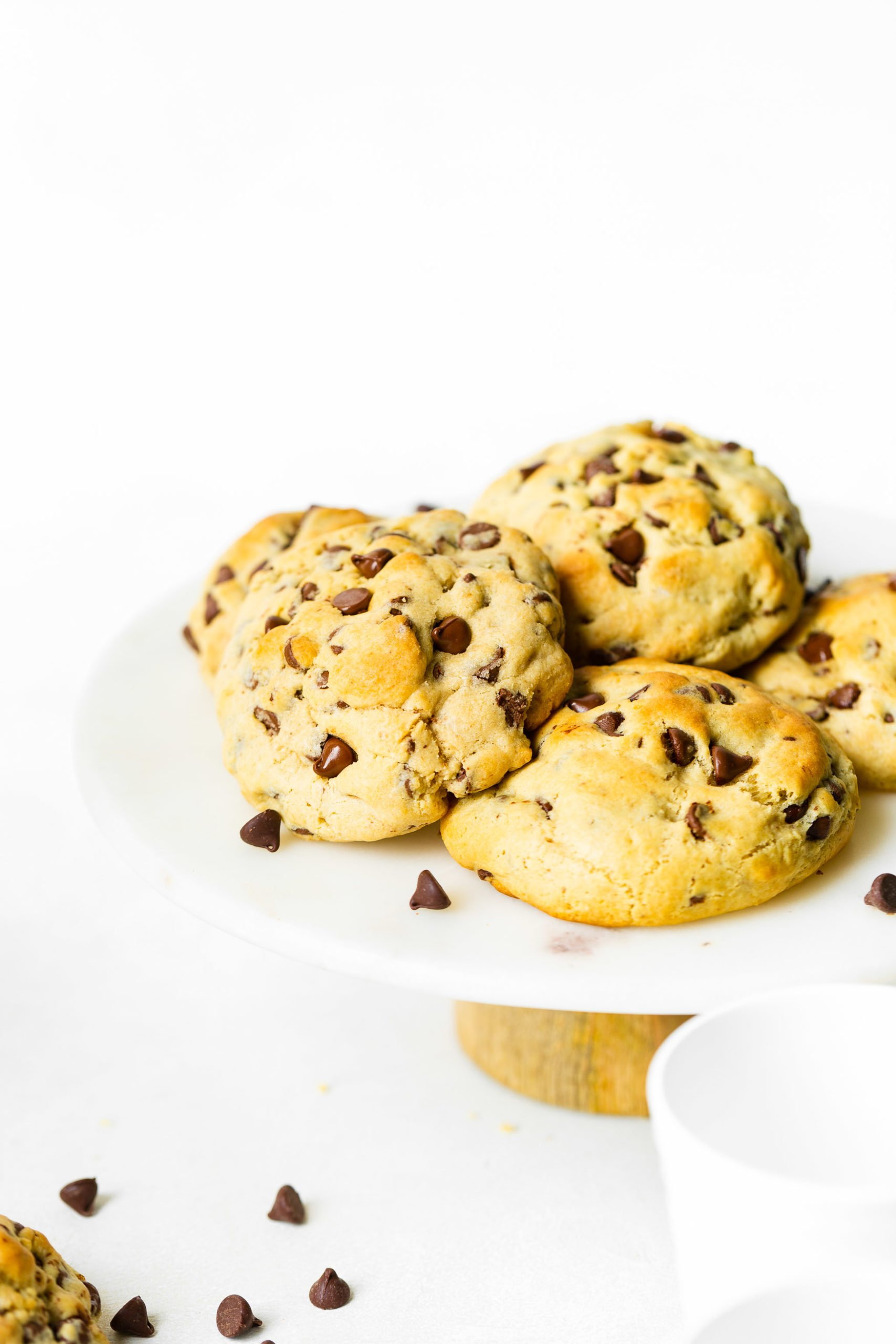 a photo of a pile of thick, perfectly golden chocolate chip cookies sitting on a white cake stand with chocolate chips scattered around.
