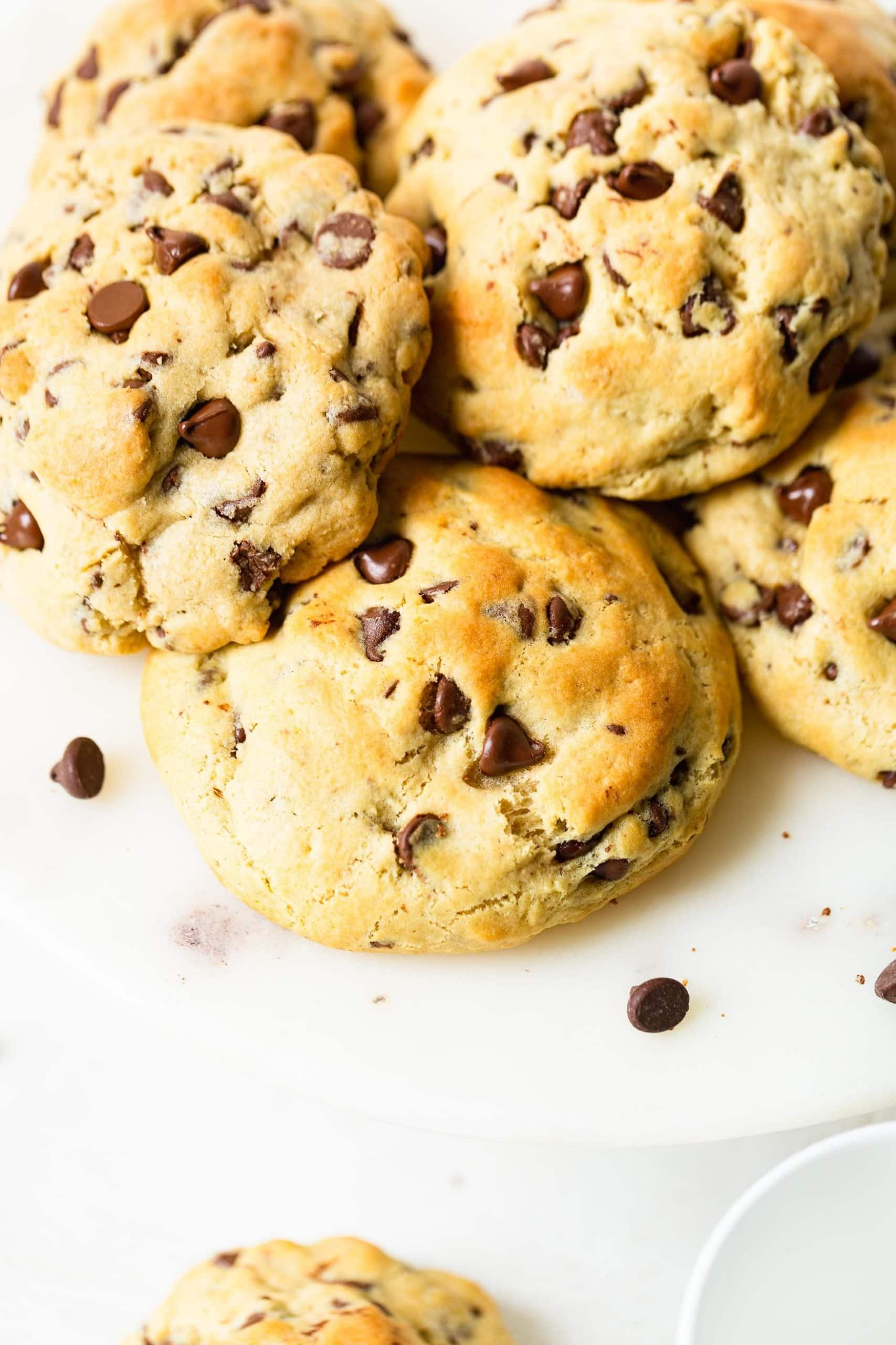 a photo of a pile of thick golden chocolate chip cookies.