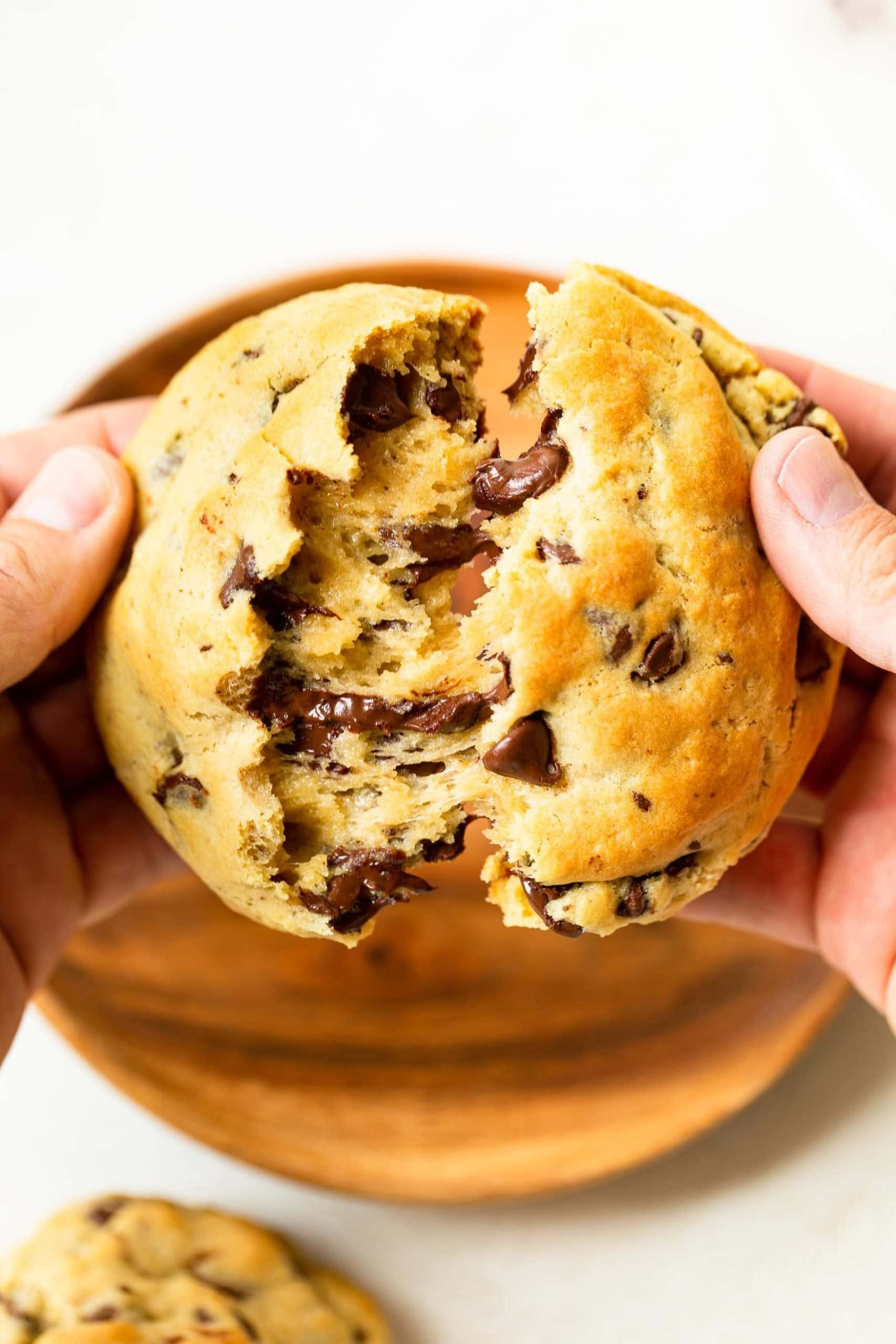 a photo of something tearing apart a gooey warm thick chocolate chip cookie.