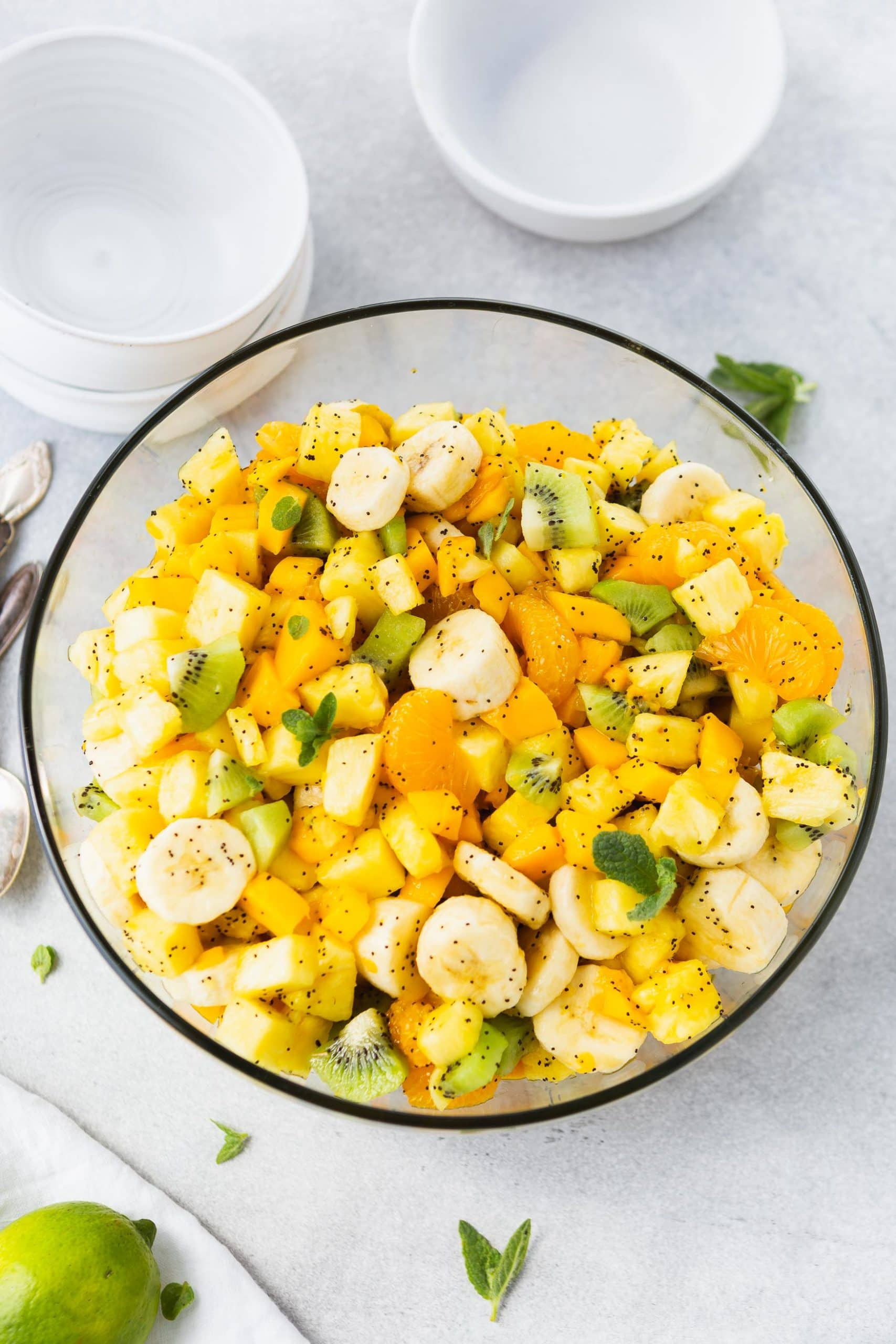 a photo taken from above a glass bowl full of a beautiful tropical fruit salad covered in a honey lime poppy seed dressing.