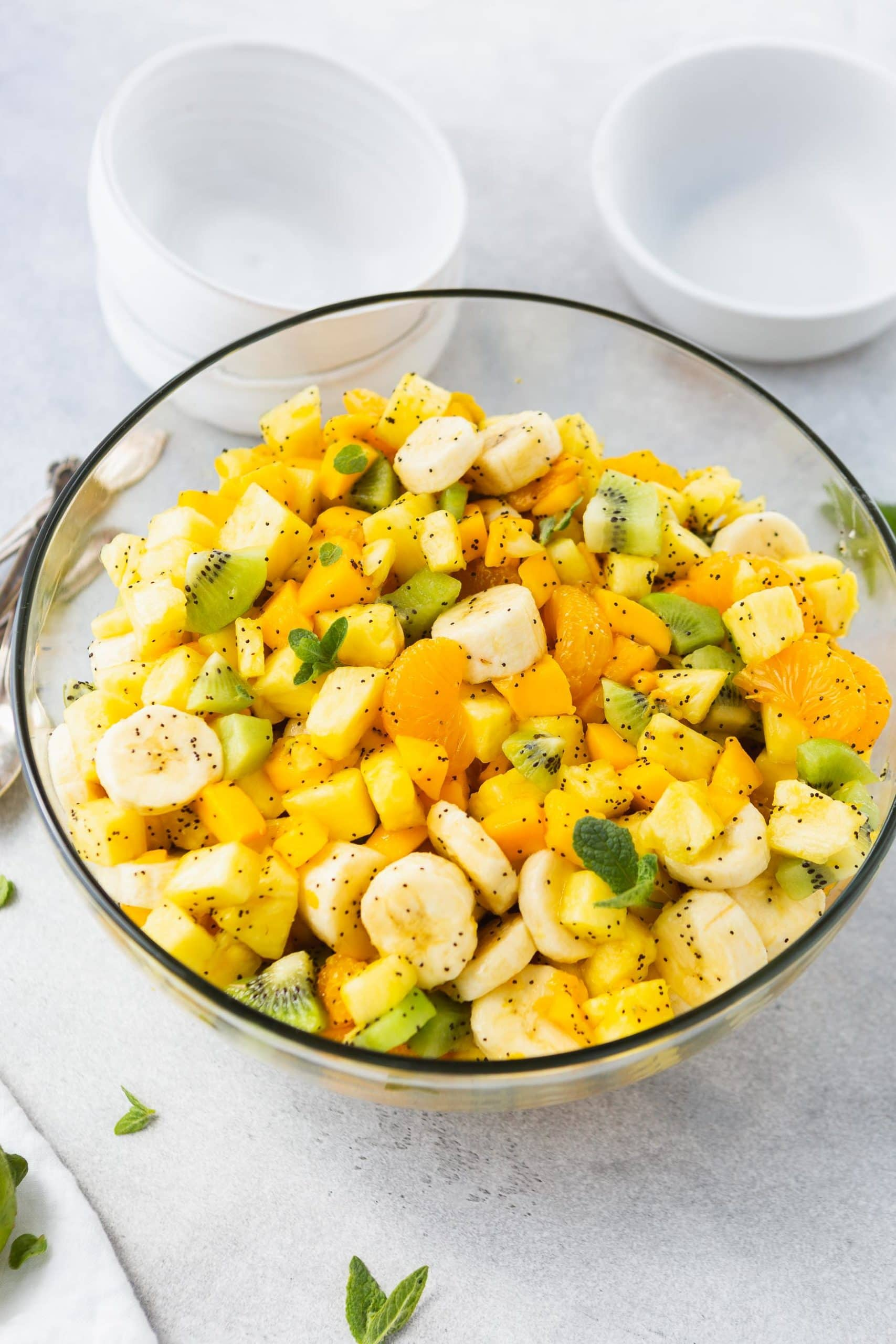 a photo of a glass bowl full of chopped tropical fruits like pineapple, mandarin oranges, bananas, and kiwi covered in a honey poppy seed dressing.