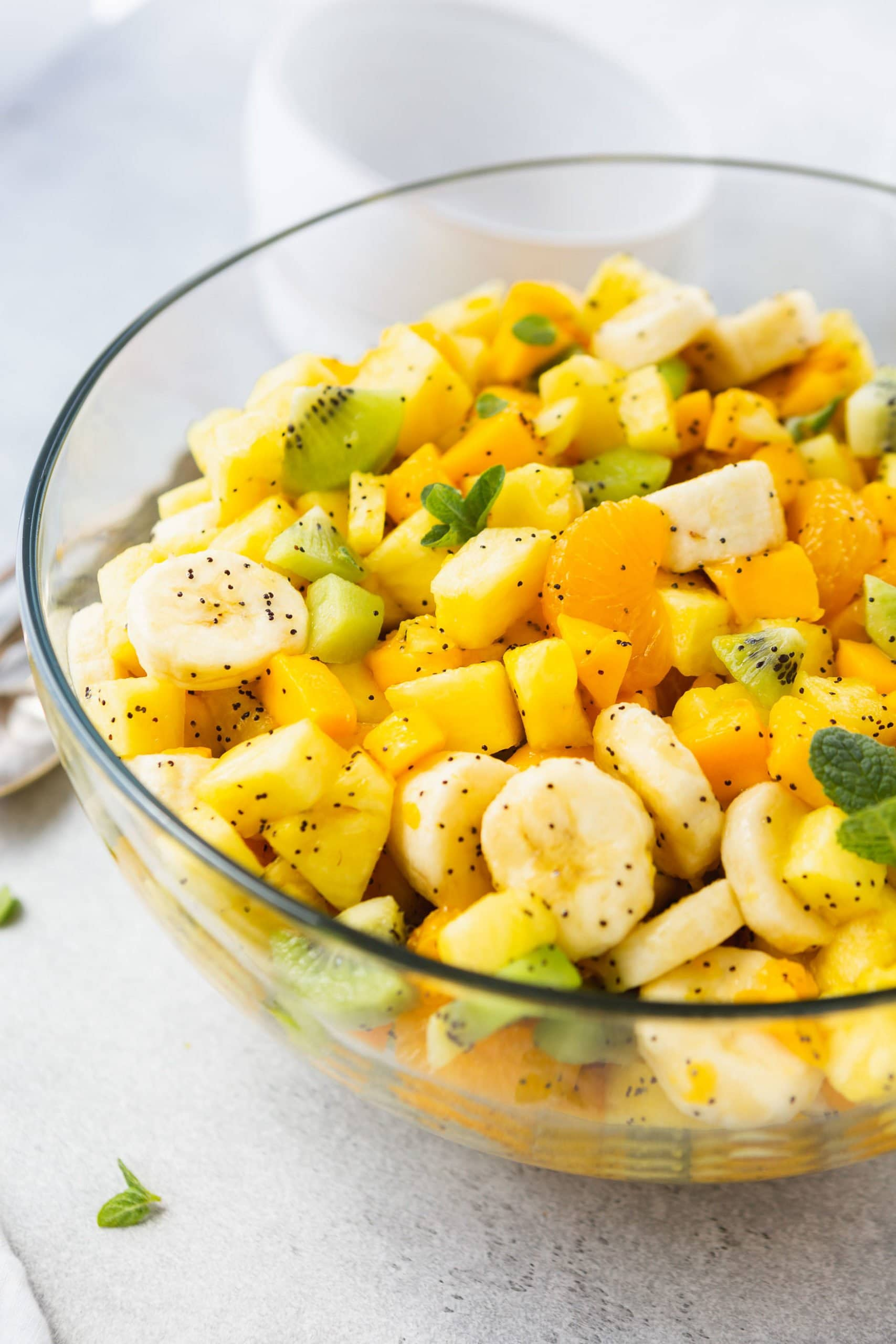 a glass bowl full of chopped up tropical fruits - mandarin oranges, kiwi, pineapple, bananas - all mixed in a bowl and coated in a poppy seed dressing.