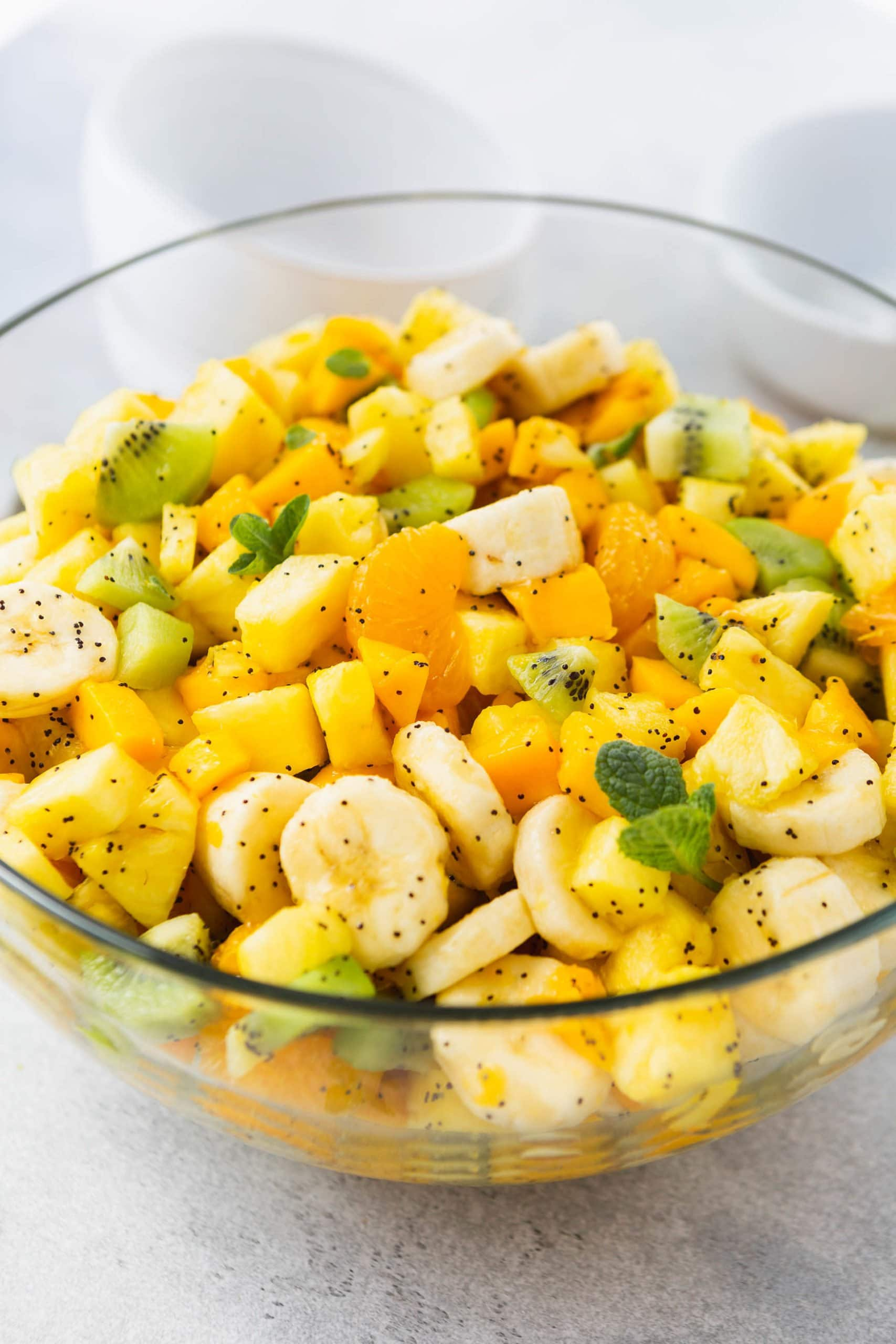 a glass bowl full of chopped up tropical fruit coated in a poppy seed honey lime dressing.