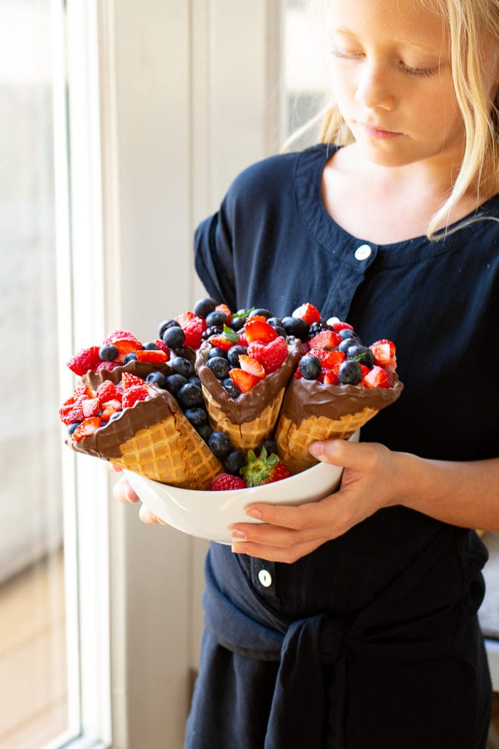 My daughter holding a bowl of waffle cones filled with berries.