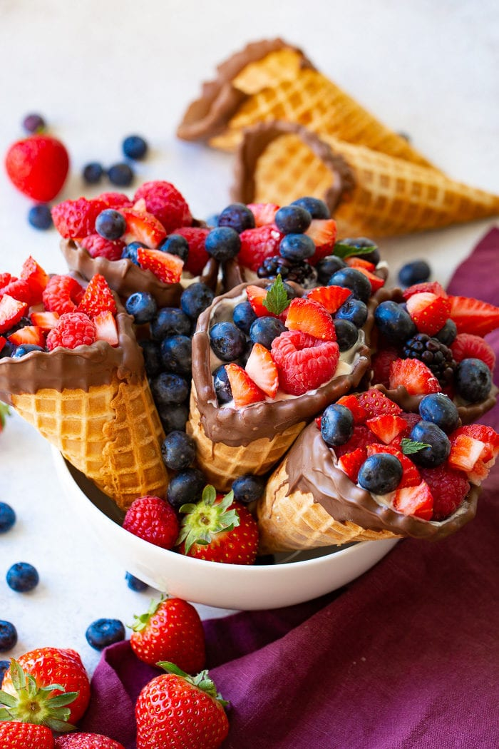 A bowl of waffle cones filled with yogurt, strawberries, blueberries & raspberries with 2 waffle cones in the background.