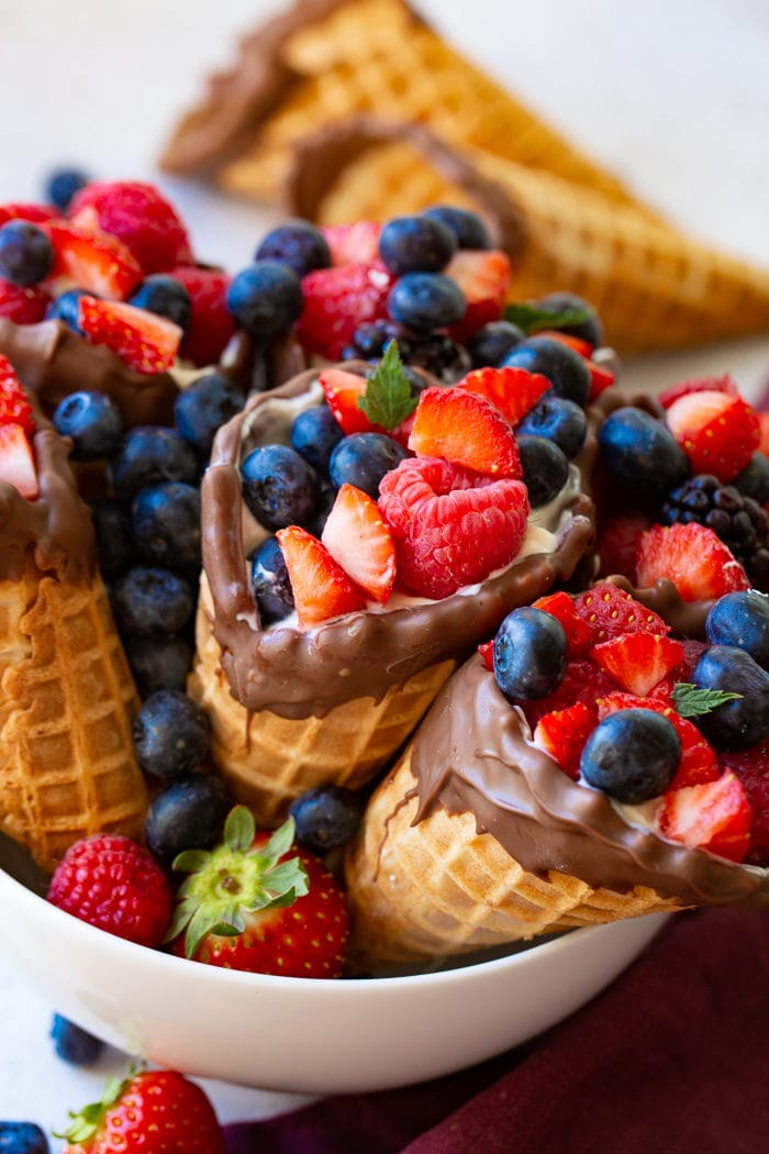 A bowl filled with fresh berries and waffle cones filled with yogurt and berries.