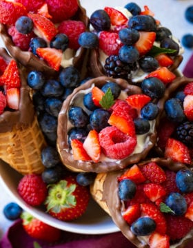 A white bowl with chocolate dipped cones filled with yogurt and fresh berries.