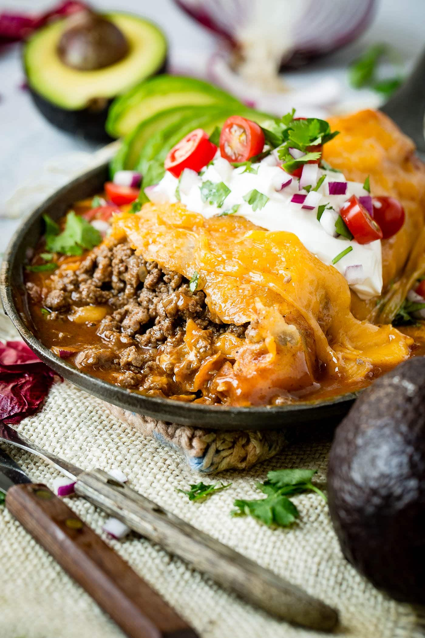 a photo of a large burrito that has been cut into to show the ground beef in a cast iron skillet topped with a sauce and melted cheese and garnished with sour cream, diced red onions, chopped cilantro and sliced grape tomatoes with some avocado slices on the side.