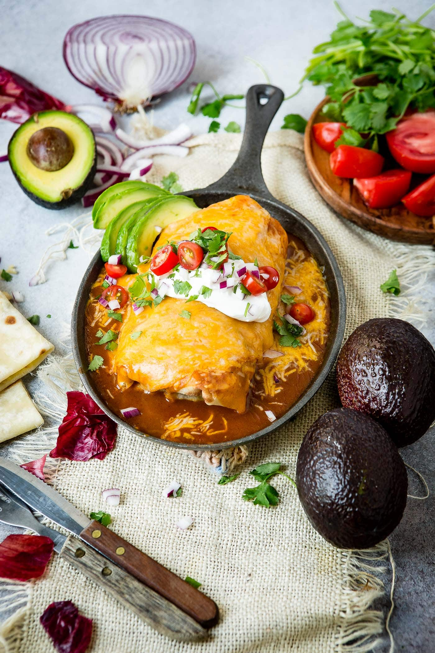 a photo of a large burrito in a cast iron skillet topped with a sauce and melted cheese and garnished with sour cream, diced red onions, chopped cilantro and sliced grape tomatoes with some avocado slices on the side. All the ingredients are scattered around the cast iron skillet.