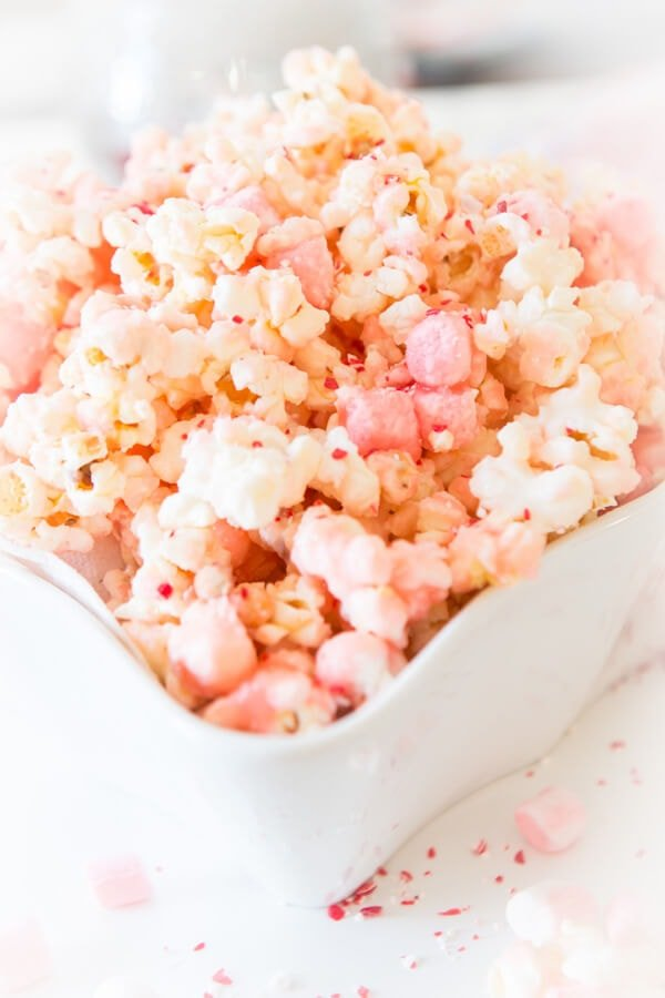 It's the holidays and you need something simple to pack up for teachers or to snuggle up and eat for movies like this white chocolate peppermint popcorn. ohsweetbasil.com