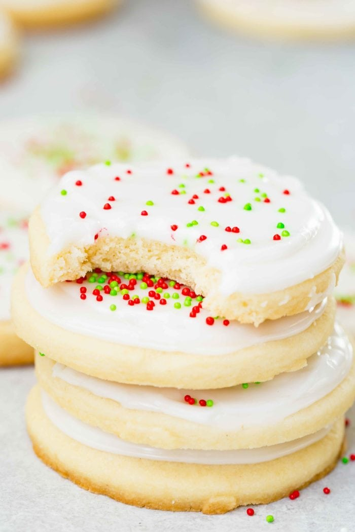 a photo of a stack of four sugar cookies with white frosting and red and green sprinkles with a bite out of the top cookie