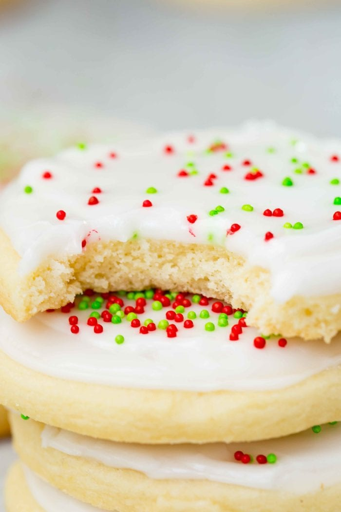 a closeup photo of a stack of sugar cookies with white frosting and red and green sprinkles with a bite out of the top cookie