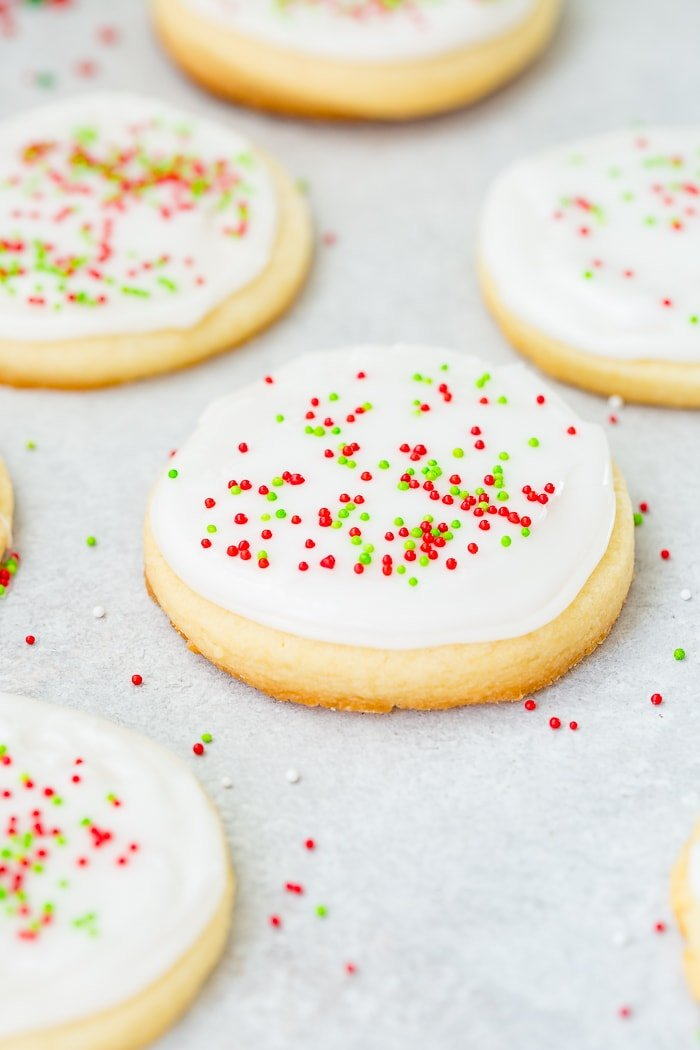 A photo of several round sugar cookies with white royal icing and red and green sprinkles