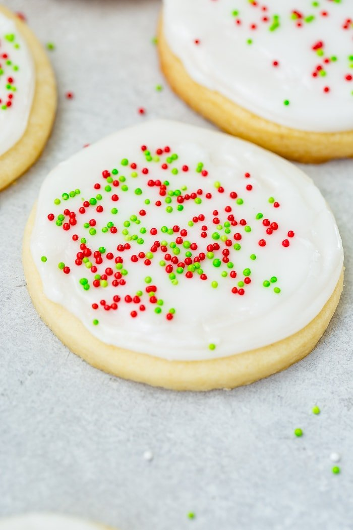A photo of a sugar cookie frosted with white royal icing with red and green sprinkles