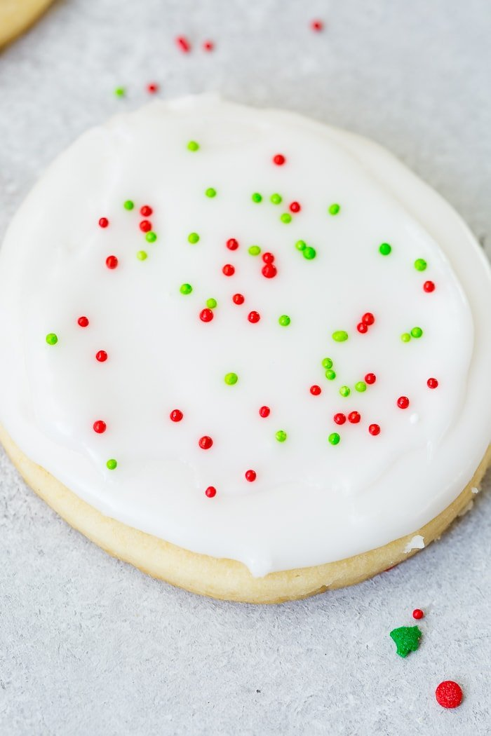 A closeup photo of a sugar cookie frosted with white royal icing with red and green sprinkles