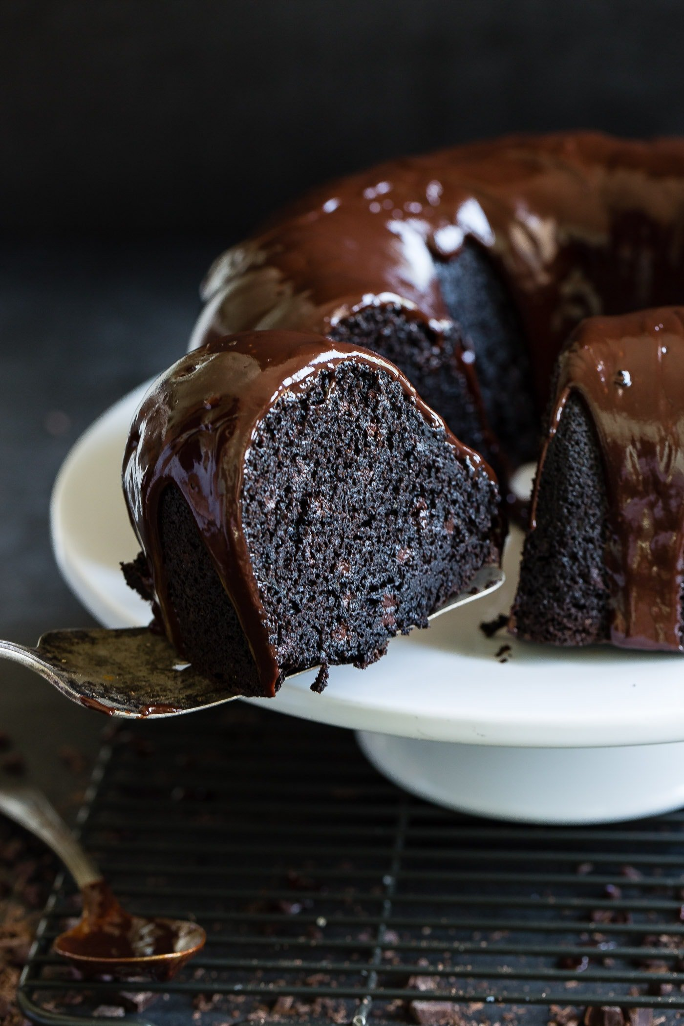 A slice of zucchini chocolate bundt cake being removed from the cake. The inside of the cake is dark, moist chocolate and there is a chocolate glaze on top of the cake.