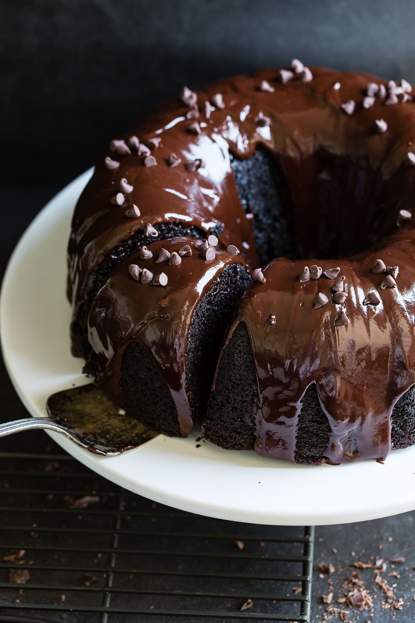 A chocolate zucchini bundt cake with chocolate glaze. The cake is on a white cake plate and a cake server is resting under a piece that has been cut.