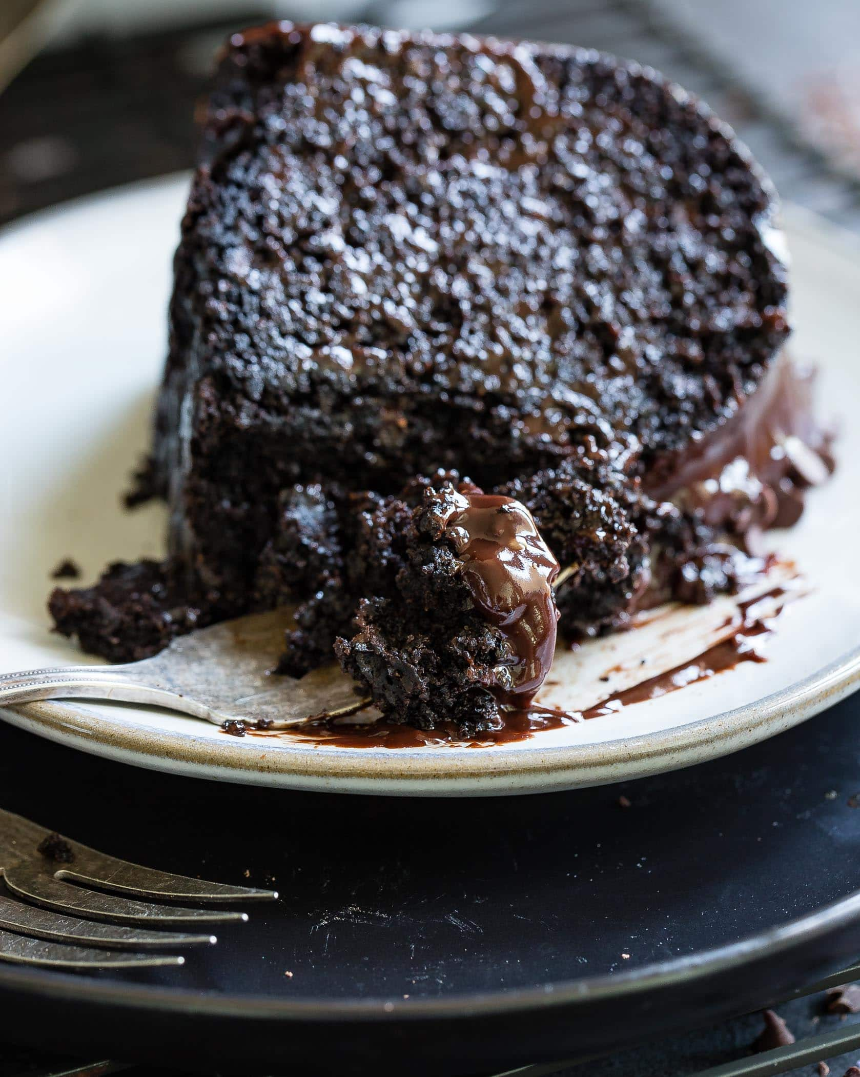 A slice of zucchini chocolate bundt cake on a white dessert plate. The cake is dark, moist chocolate with a chocolate glaze. A fork is beside the plate.