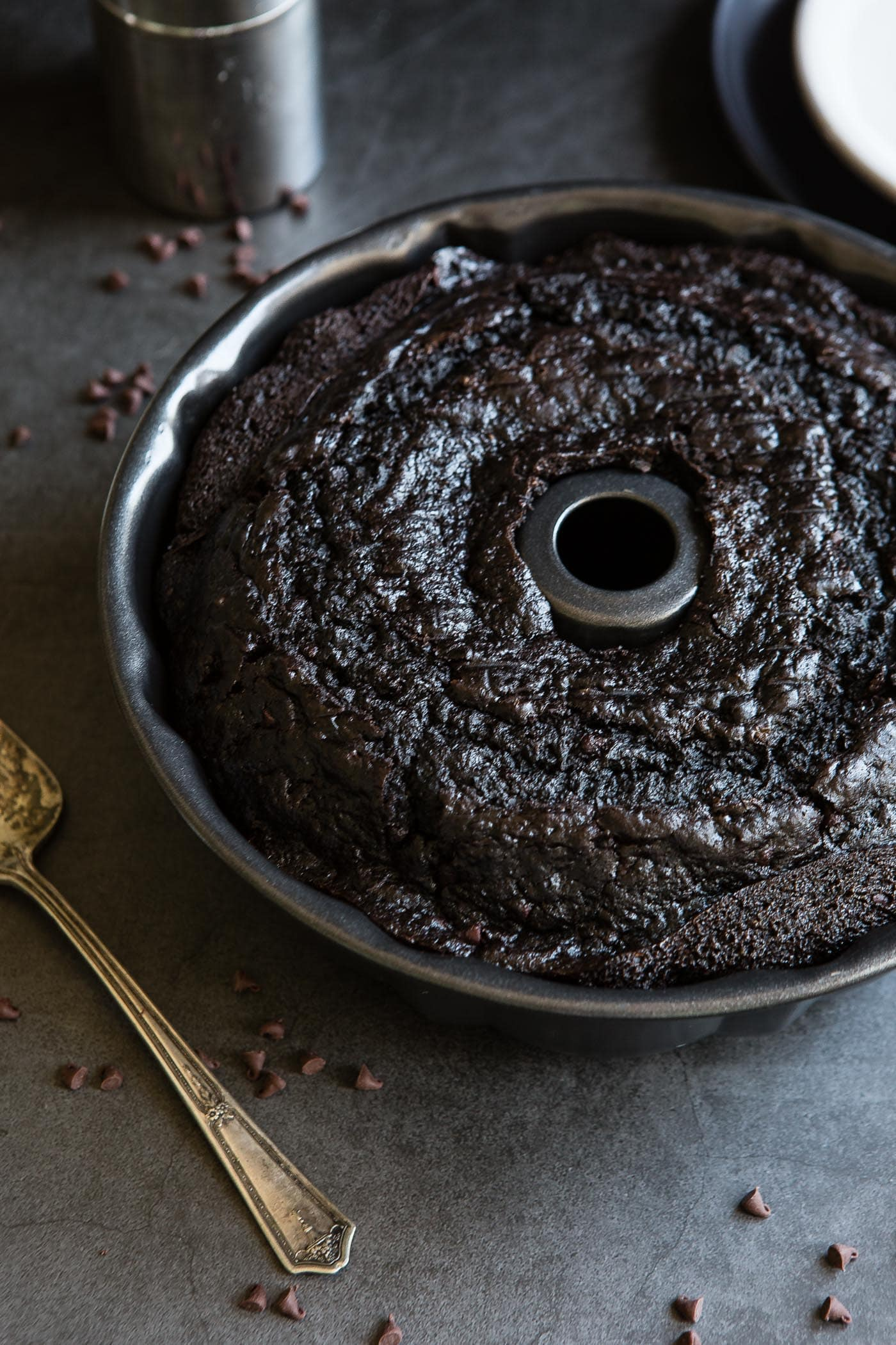 A baked zucchini chocolate bundt cake in the bundt pan. Bits of chocolate and a cake server are next to the cake.