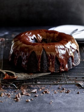 A zucchini chocolate bundt cake with a rich chocolate glaze. The cake is on a wire cooling rack and has mini chocolate chips scattered under and around the rack.